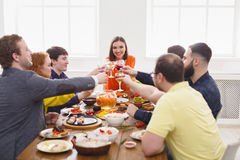 People say cheers clink glasses at festive table dinner party. Group of people clink glasses, saying cheers, eat healthy meals at party dinner table in cafe Royalty Free Stock Images