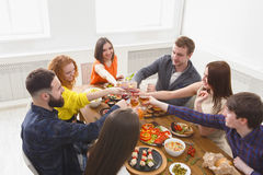 People say cheers clink glasses at festive table dinner party. Group of people clink glasses, saying cheers, eat healthy meals at party dinner table in cafe Stock Images