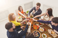 People say cheers clink glasses at festive table dinner party. Group of people clink glasses, saying cheers, eat healthy meals at party dinner table in cafe Stock Image