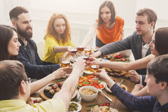 People say cheers clink glasses at festive table dinner party. Group of people clink glasses, saying cheers, eat healthy meals at party dinner table in cafe stock photo