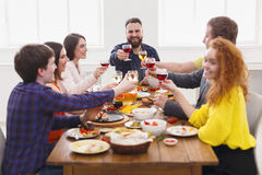 People say cheers clink glasses at festive table dinner party. Happy friends clink glasses, saying cheers at party dinner table in cafe, restaurant or at home Royalty Free Stock Photo