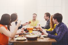 People say cheers clink glasses at festive table dinner party stock image