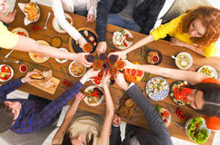 People say cheers clink glasses at festive table dinner party. People clink glasses, saying cheers, eat healthy meals at party dinner table. Friends celebrate Royalty Free Stock Photo