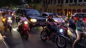Scooters, motorcycles, cars, traffic and people at night Ho Chi Minh City, Vietnam. PEOPLE ON SCOOTERS WAITING AT TRAFFIC LIGHTS ON THE NIGHT TIME STREETS OF HO stock video