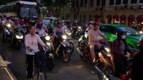 Scooters, mopeds, motorcycles, cars, traffic and people, Ho Chi Minh City, Vietnam. PEOPLE ON SCOOTERS WAITING AT TRAFFIC LIGHTS ON THE NIGHTTIME STREETS OF HO stock video