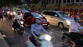 Scooters, motorcycles, cars, traffic and people, Ho Chi Minh City, Vietnam. PEOPLE ON SCOOTERS WAITING AT TRAFFIC LIGHTS ON THE STREETS OF HO CHI MINH CITY OR stock video