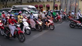 Scooters, motorcycles, cars, traffic and people, Ho Chi Minh City, Vietnam. PEOPLE ON SCOOTERS WAITING AT TRAFFIC LIGHTS ON THE STREETS OF HO CHI MINH CITY OR stock footage