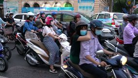 Scooters, motorcycles, cars, traffic and people, Ho Chi Minh City, Vietnam. PEOPLE ON SCOOTERS WAITING AT TRAFFIC LIGHTS ON THE STREETS OF HO CHI MINH CITY OR stock video footage