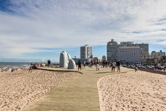 People at the sculpture La Mano in Punta Del Este, Uruguay. Punta Del Este, Uruguay - February 28th, 2018: People taking photos and sefies at La Mano, the Stock Image