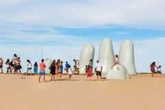 People at the sculpture La Mano in Punta Del Este, Uruguay. Punta Del Este, Uruguay - February 28th, 2018: People taking photos and sefies at La Mano, the Royalty Free Stock Images