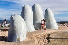 People at the sculpture La Mano in Punta Del Este, Uruguay. Punta Del Este, Uruguay - February 28th, 2018: Three young women taking photos and sefies at La Mano Royalty Free Stock Photo