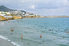 People in the Sea. SPAIN,SITGES -25.08.17 : beach area with tourists in the sea in Spain - summer holiday  Concept Royalty Free Stock Image