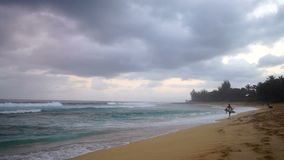 Surfers Walk Ocean Shoreline Beach Cloudy Stormy Day Shore Surf. People search for the right time for entering the surf on the beach stock video footage