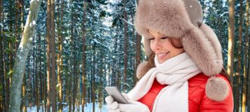 Close up of woman with smartphone in winter hat royalty free stock images