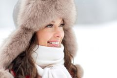 Close up of happy woman in winter fur hat outdoors Royalty Free Stock Image