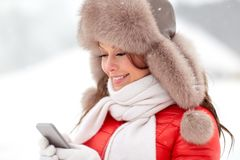 Happy woman in winter fur hat with smartphone Stock Photography