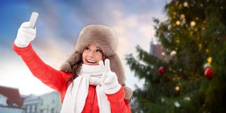 Woman taking selfie over christmas tree royalty free stock photography