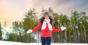 Happy woman in fur hat over winter forest royalty free stock photos
