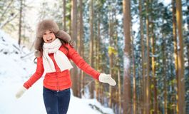 Happy woman in fur hat over winter forest royalty free stock images