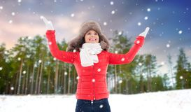 Happy woman in fur hat over winter forest stock image