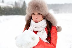 Happy woman with snow in winter fur hat outdoors. People, season and leisure concept - happy woman in winter fur hat blowing on snow in her hands outdoors Stock Photo