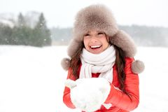 Happy woman with snow in winter fur hat outdoors. People, season and leisure concept - happy woman in winter fur hat holding snow in her hands outdoors Royalty Free Stock Photography