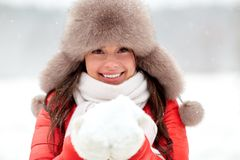 Happy woman with snow in winter fur hat outdoors. People, season and leisure concept - happy woman in winter fur hat holding snow in her hands outdoors Stock Photos