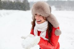 Happy woman with snow in winter fur hat outdoors. People, season and leisure concept - happy woman in winter fur hat holding snow in her hands outdoors Royalty Free Stock Images
