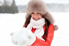 Happy woman with snow in winter fur hat outdoors. People, season and leisure concept - happy woman in winter fur hat holding snow in her hands outdoors Royalty Free Stock Photos