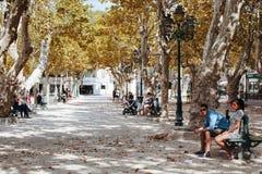 People seat in park. Saint Tropez, France - November 1, 2015: People seat in park Stock Photos