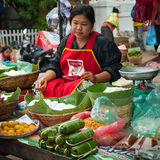 People selling food at traditional asian marketplace. Laos Stock Image