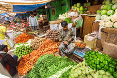 People selling vegetables in a big market with carrots, peppers, peas, tomatoes Stock Photos