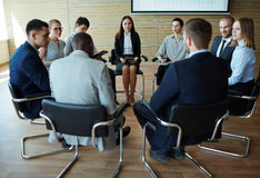 People at seminar. Businesspeople seated in circle at company seminar Royalty Free Stock Photo