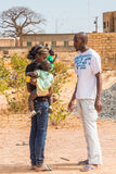 People in Senegal, Africa. LOUGA, SENEGAL - MAR 15, 2013: Unidentified Senegalese man talks to the woman with her baby. People in Senegal suffer of poverty due stock images