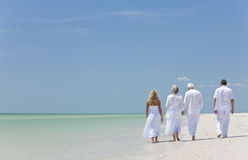 People Seniors Family Couples Generations on Beach. Rear view of four people, two seniors, couples or family generations, holding hands, walking on a tropical Stock Image