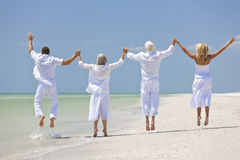 People Seniors Family Generations Jumping on Beach. Rear view of four people, two seniors, couples or family generations, holding hands, having fun and jumping Royalty Free Stock Photo