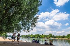 People by the Serpentine Lake at Hyde Park in the English summer Royalty Free Stock Image
