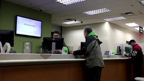 People at service counter talking to the teller Stock Image