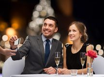 Couple with credit card at christmas restaurant. People, service and holidays concept - smiling couple paying for dinner with credit card at restaurant over stock photo