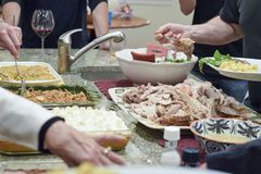People serving themselves Thanksgiving dinner. From various different casseroles and pans royalty free stock images