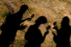 People shadows. Shadows of some people having drinks, on a grassy surface Stock Images