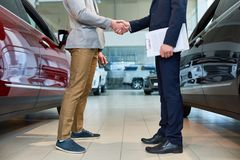 People Shaking Hands in Car Showroom. Low section side view of  handsome client shaking hands with sales manager in car showroom, after buying brand new luxury Royalty Free Stock Photo