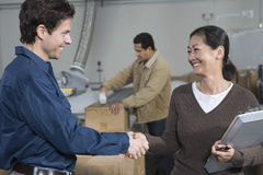 People Shaking Hands In Distribution Warehouse. Multiethnic men and women shaking hands in distribution warehouse royalty free stock photo