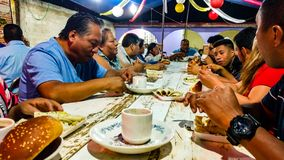 People sharing a meal at the Calenda San Pedro in San Pedro Apostal. SAN PEDRO APOSTAL, OAXACA, MEXICO-July 1, 2016. A local host family shares a meal during Royalty Free Stock Photos