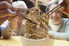 People sharing noodles, close-up Stock Photography