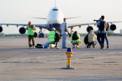 People shoot parked airplane Stock Photography