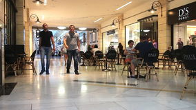 People shopping in busy mall stock footage