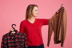People, shopping and choice concept. Beautiful lovely female with cheerful expression, holds two new outfits on hangers, can`t cho royalty free stock photos