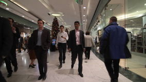 People shopping for Christmas in busy mall stock footage
