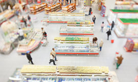 People shopping in a large supermarket. Shot with a tilt and shift lens with the focus on the racks royalty free stock images
